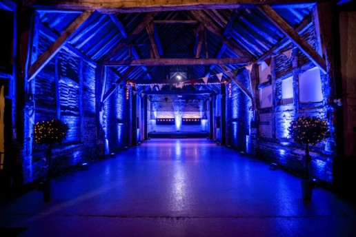 blue uplighitng in barn wedding
