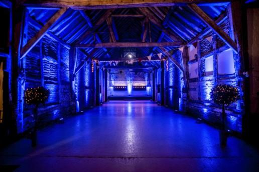 blue uplighitng in barn wedding